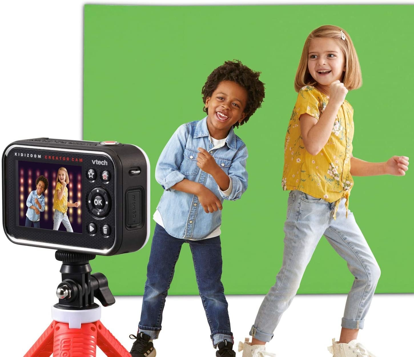 two kids in front of the green screen and the camera filming them with a light background behind them