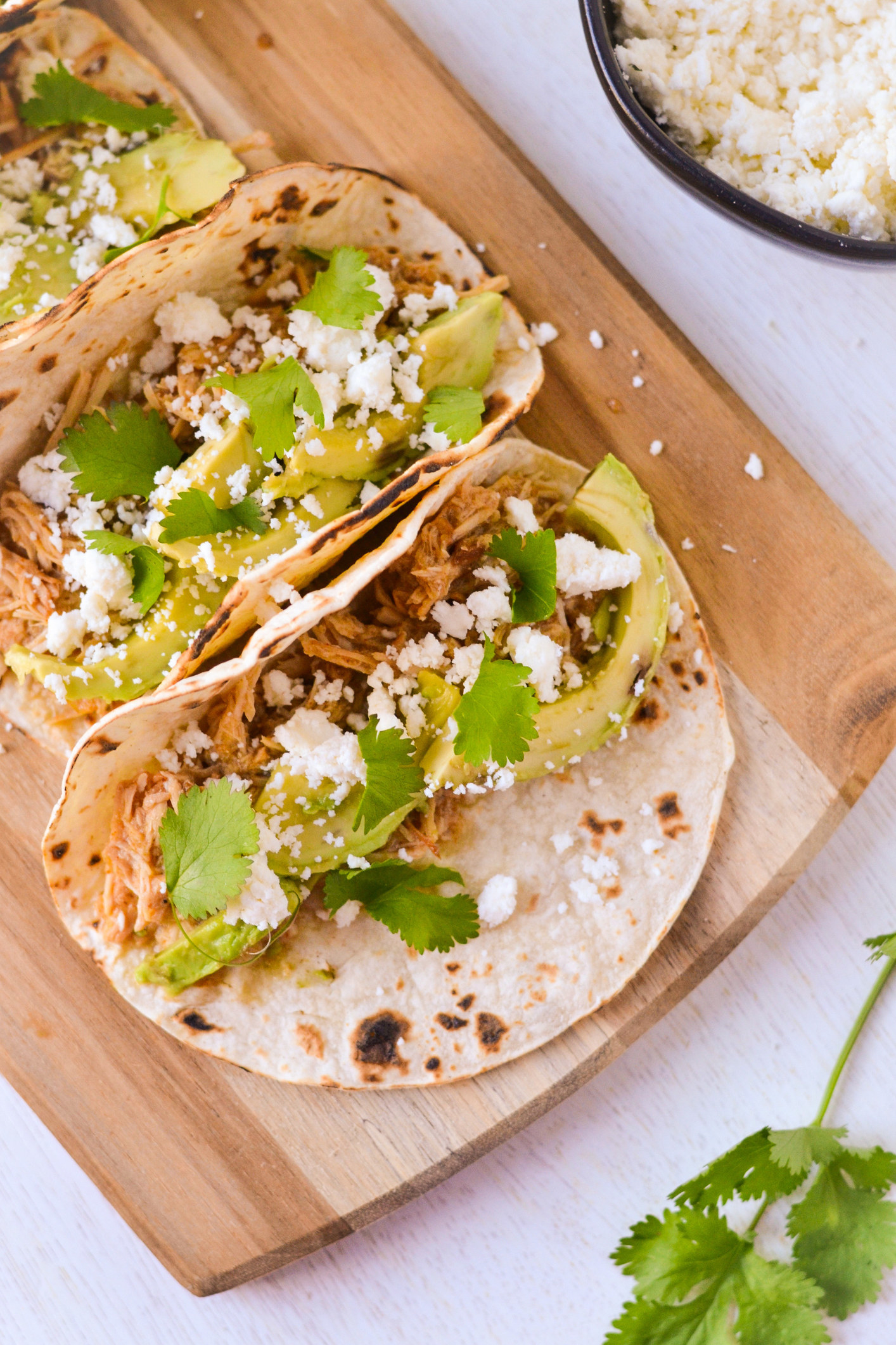 Three tortillas filled with shredded chicken, avocado, cheese, and cilantro.