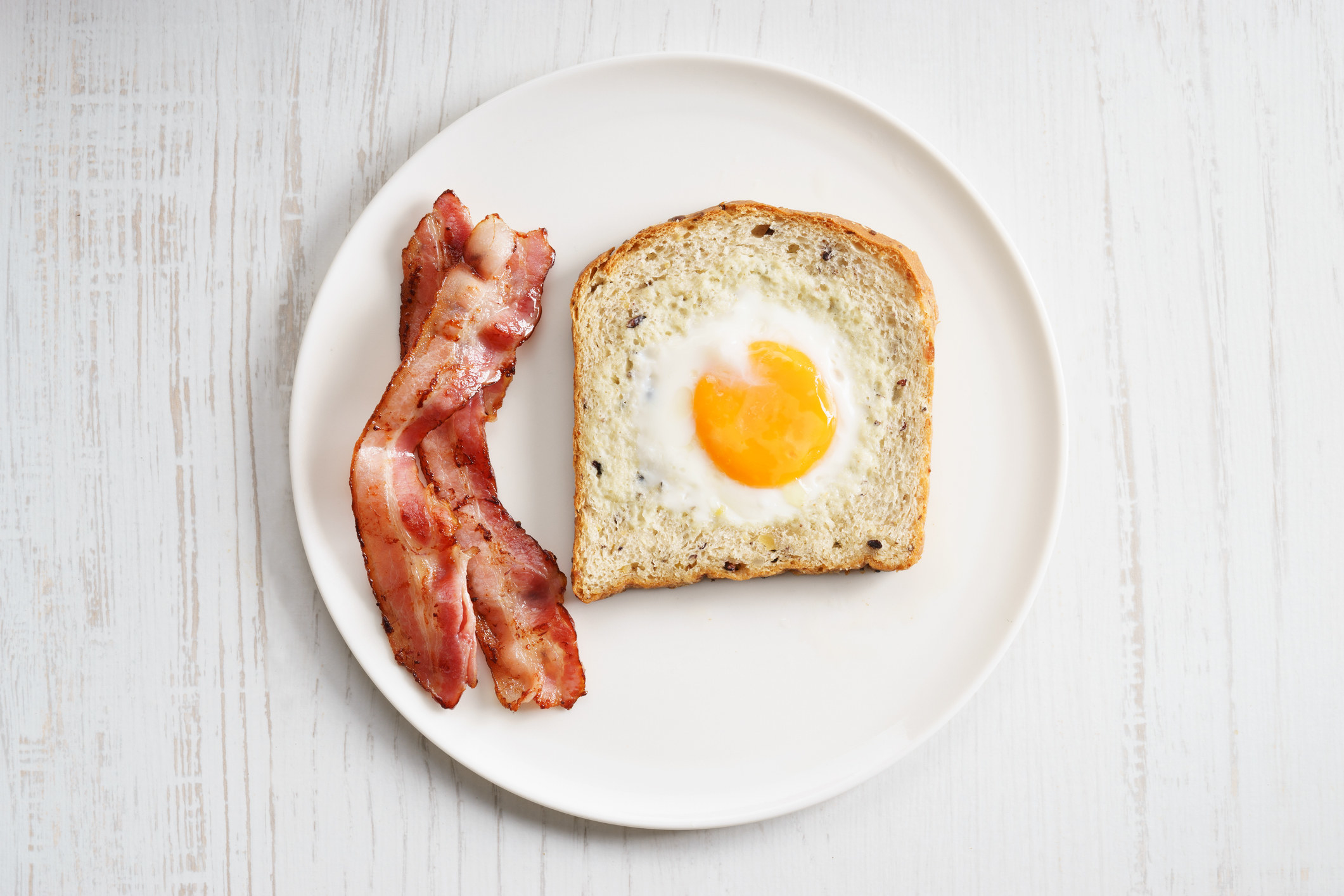 An egg baked in a slice of toast with two pieces of bacon on the side.