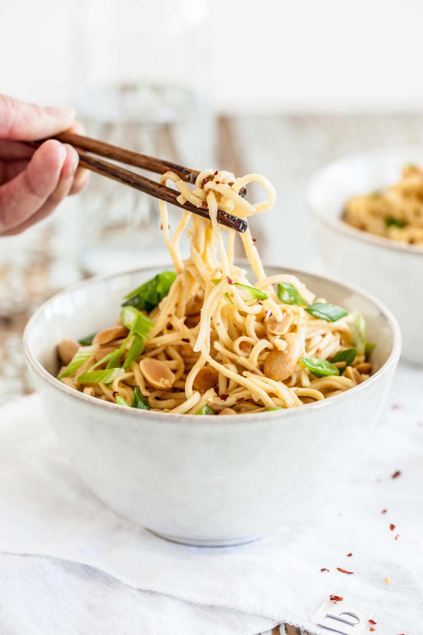 Someone eating peanut noodles with chopsticks.