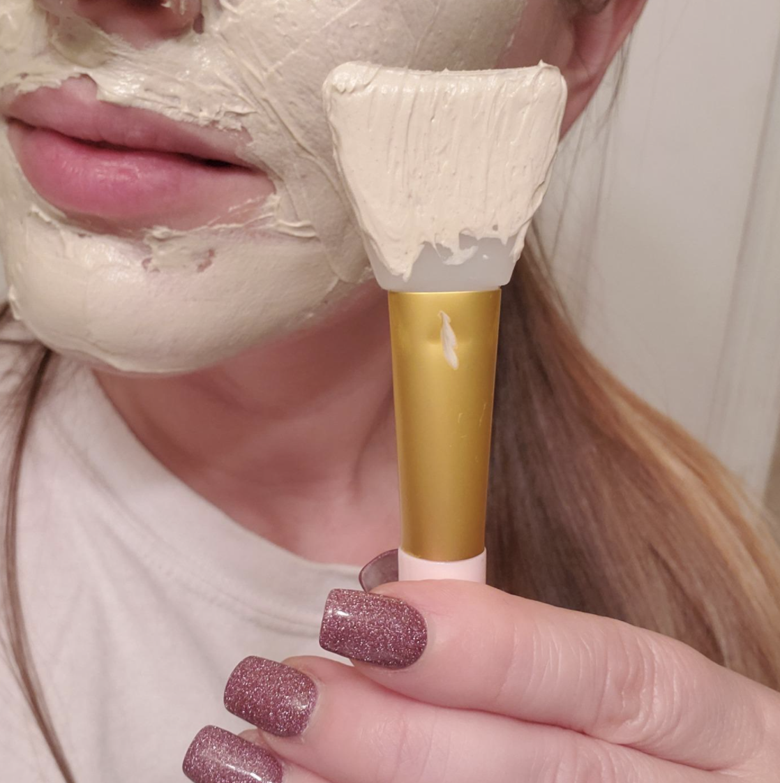 Reviewer holding the silicone brush up to their face that's covered in a mask