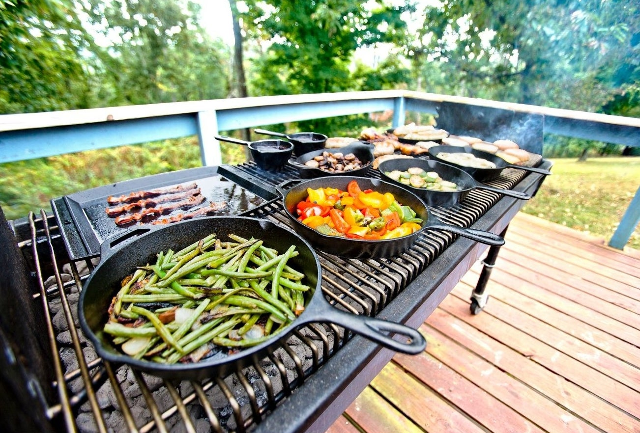 lots of cast iron skillets cooking vegetables while on a grill