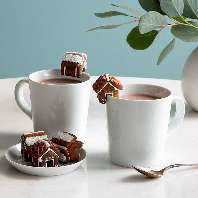 Tiny gingerbread house cookies placed on edge of cups