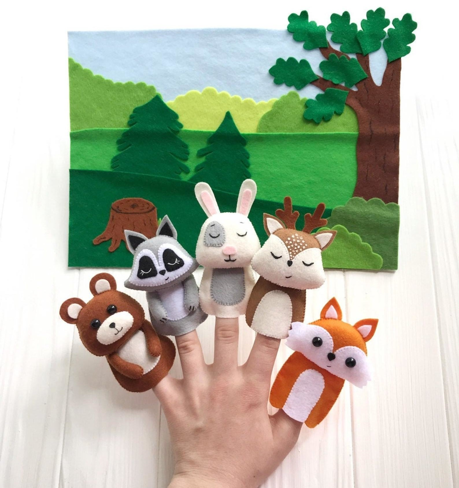 Model's hand with five different felt animal finger puppets on each finger