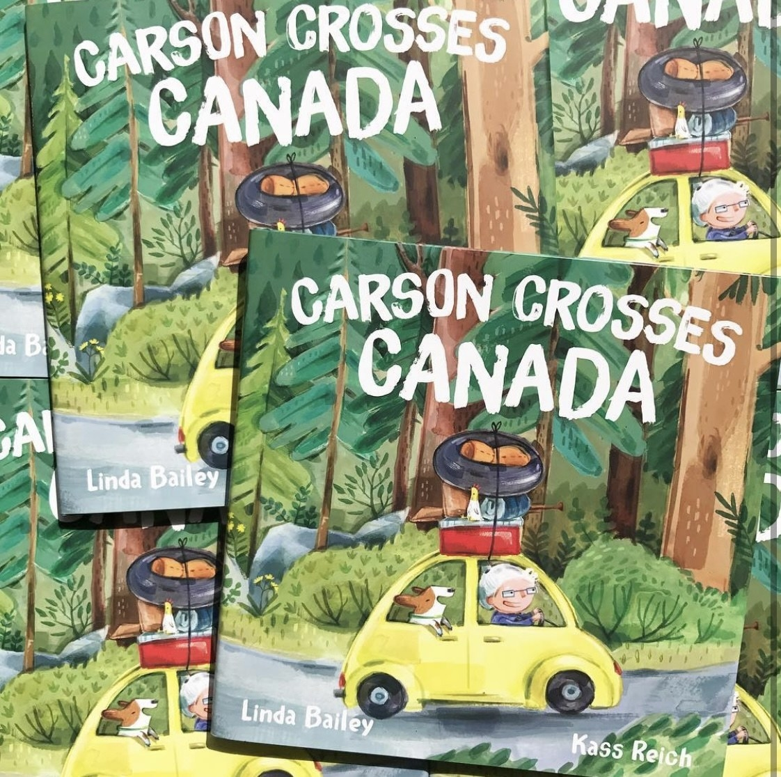 multiple copies of Carson Crosses Canada laid on top of each other with the illustration on the cover of an elderly woman and her dog in a yellow car driving through the forest