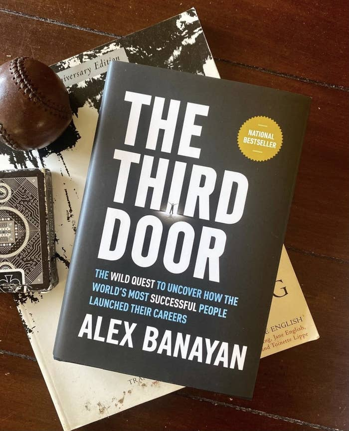 The Third Door book on a table with a deck of cards and a baseball