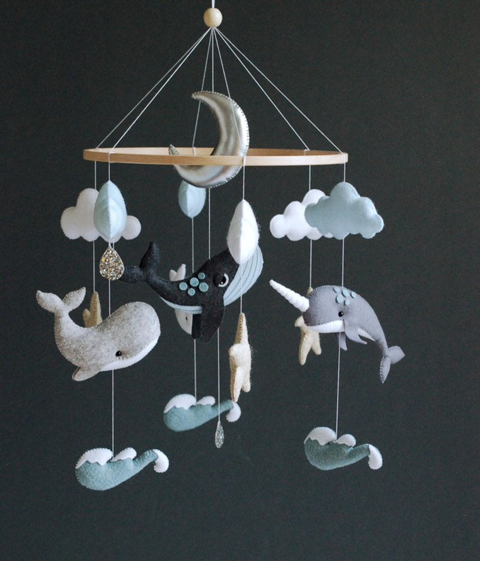 A mobile of various gray and blue whales and waves with a silver moon at the center