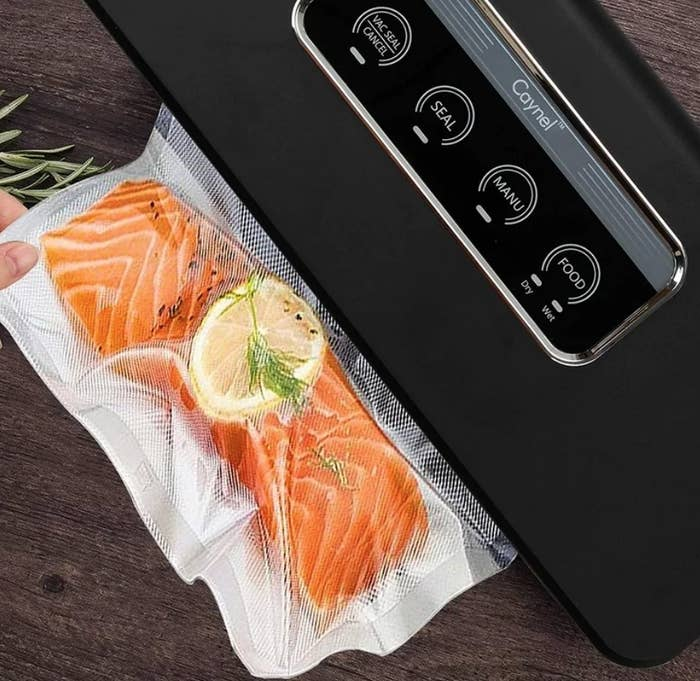 Black vacuum sealer sealing salmon in plastic wrap