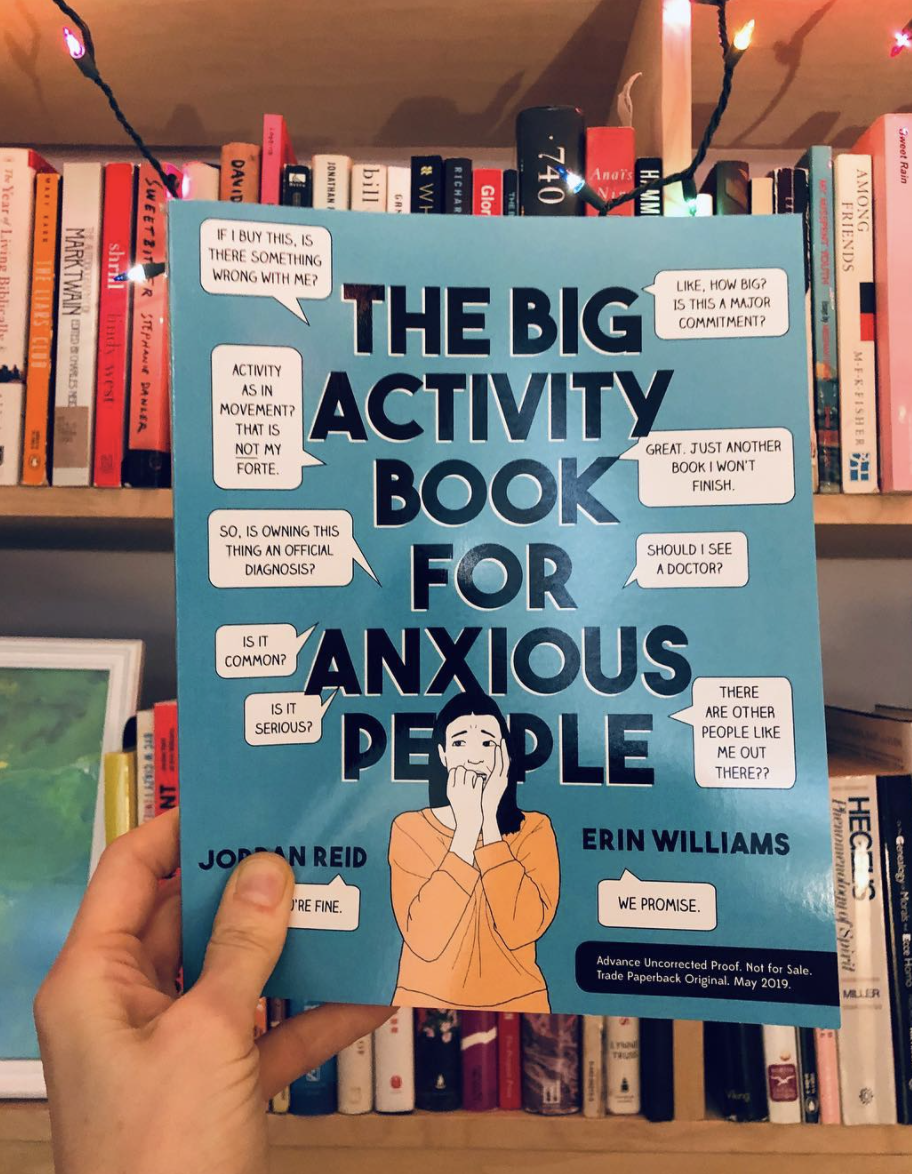 hand holding The Big Activity Book for Anxious People in front of a bookshelf