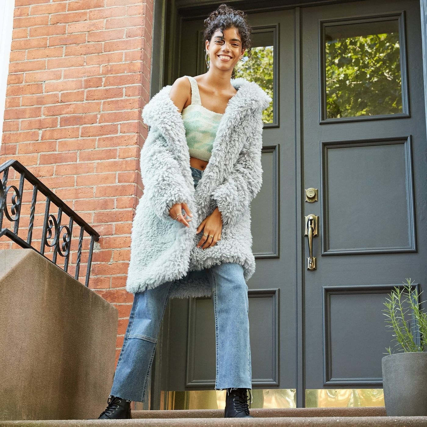perosn wearing a light blue faux fur jacket over a crop top and blue jeans