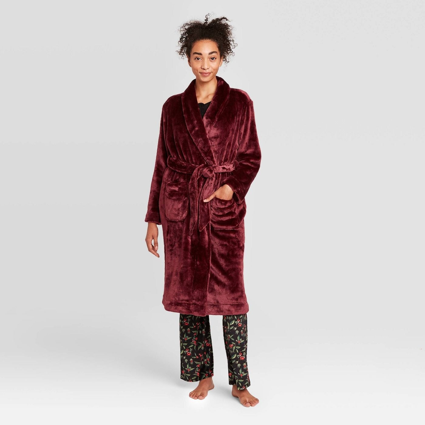 person wearing a burgundy plush robe over pajama pants