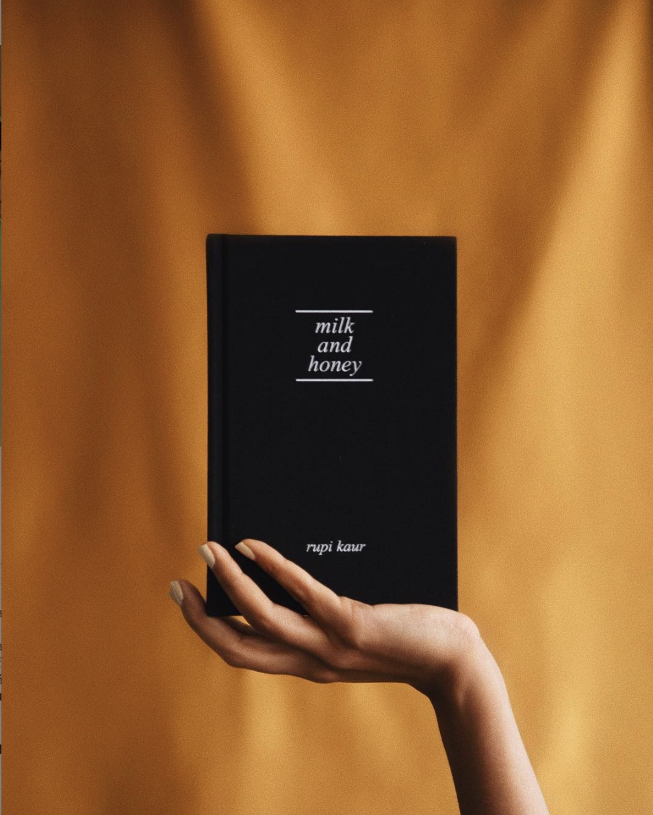 hand holding the book Milk and Honey in an upright position in front of a yellow piece of fabric