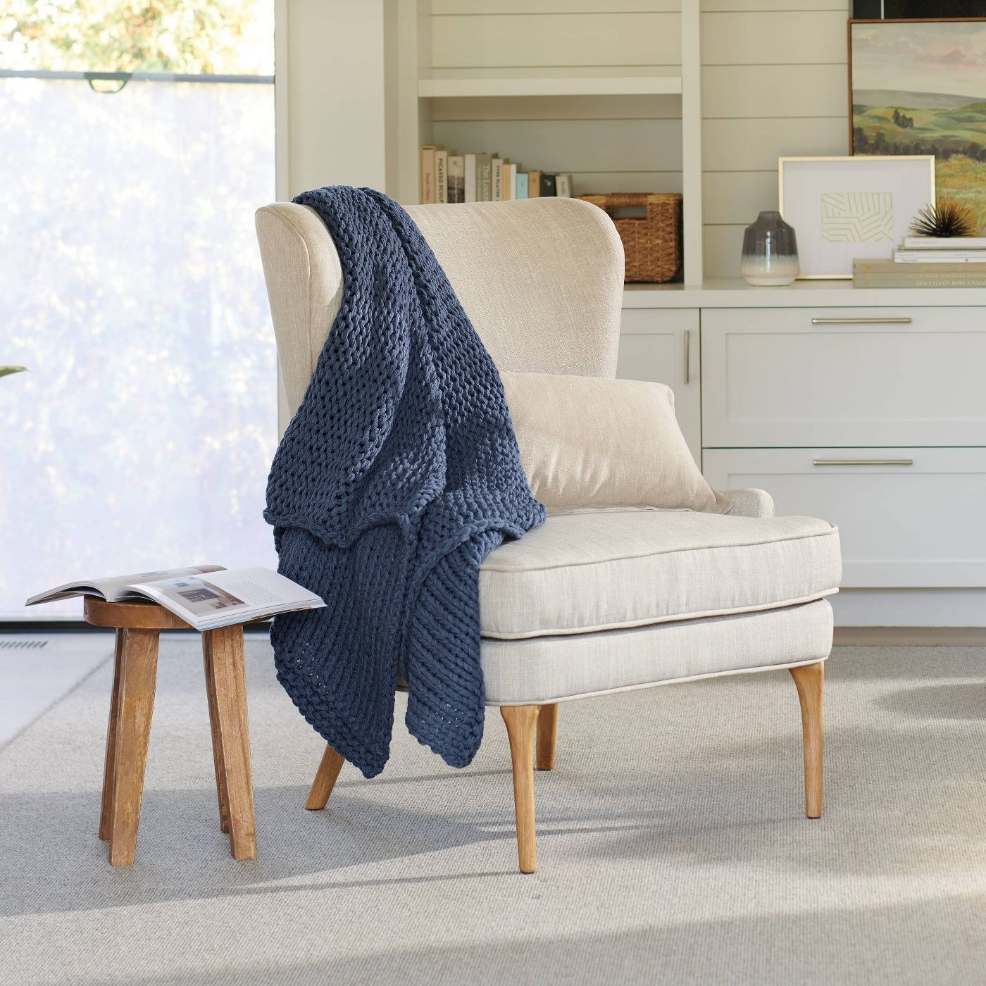 blue chunky knit blanket draped over a white accent chair
