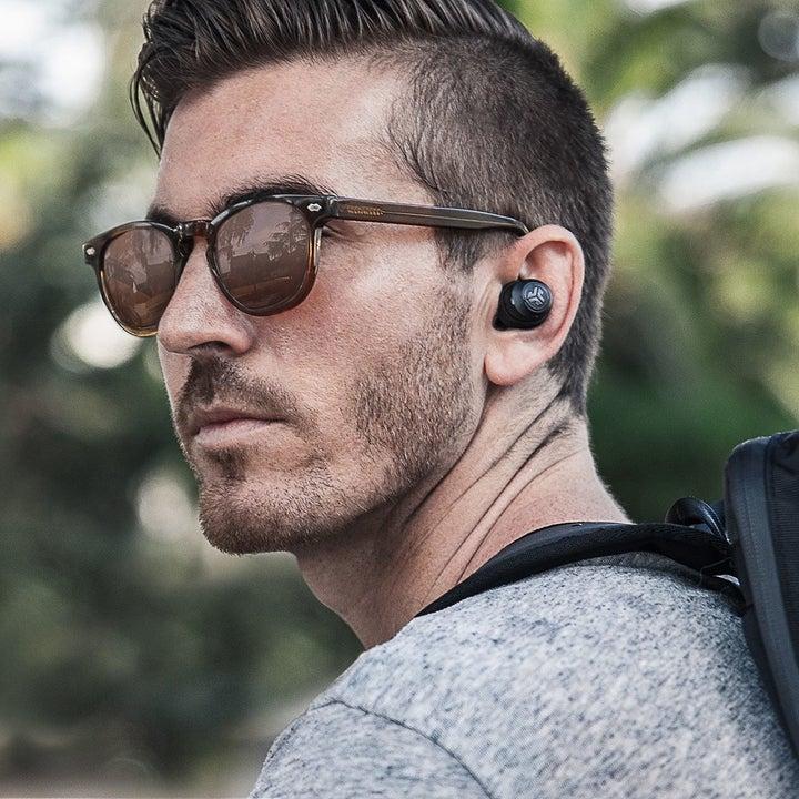 person wearing one black Jbuds earbud in their ear