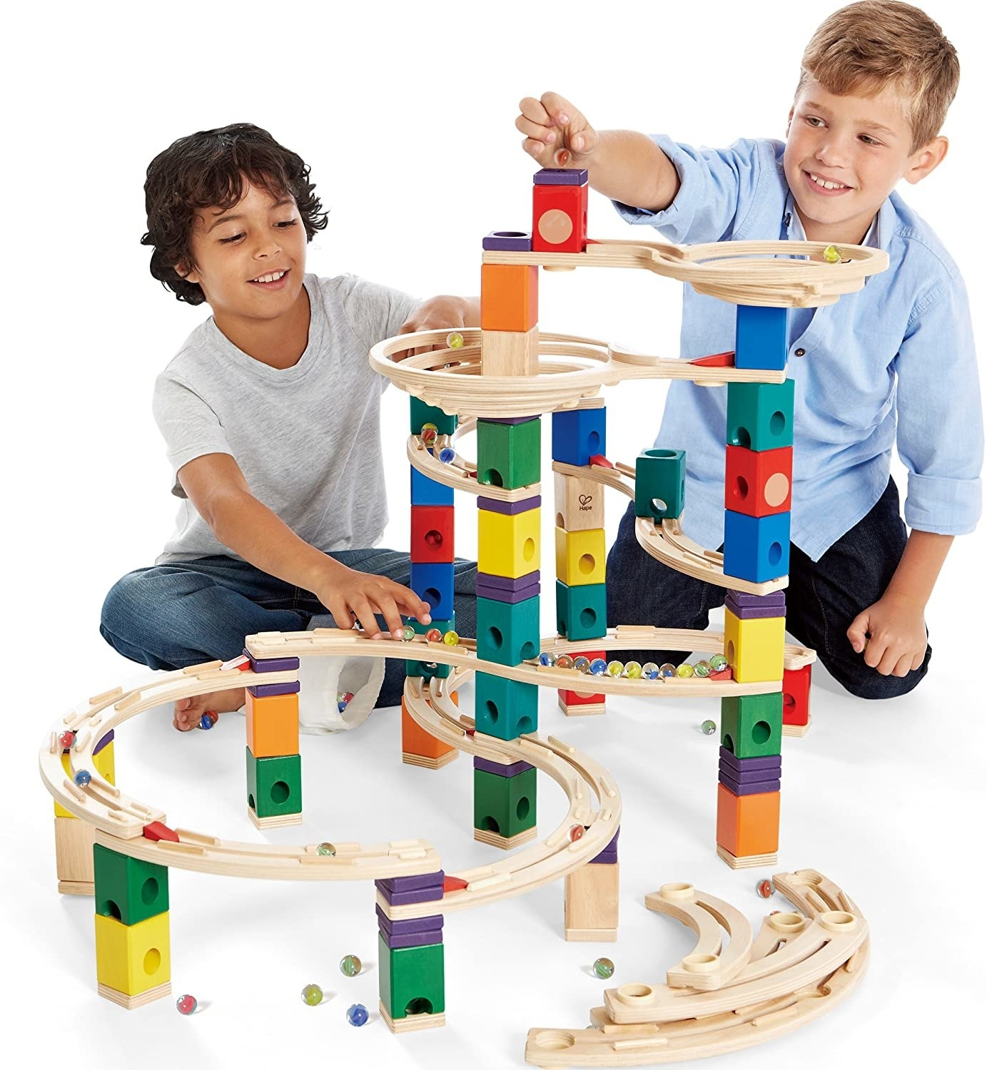 Two boys play with marbles on a wooden marble run set.