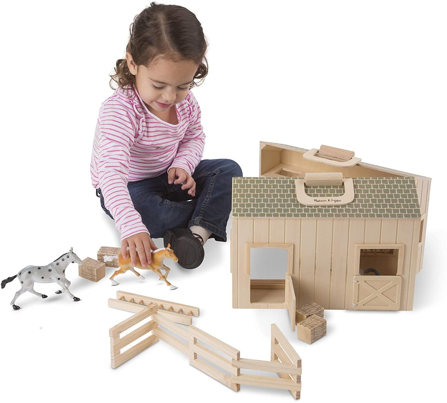 A child plays with a toy stable with two toy horses