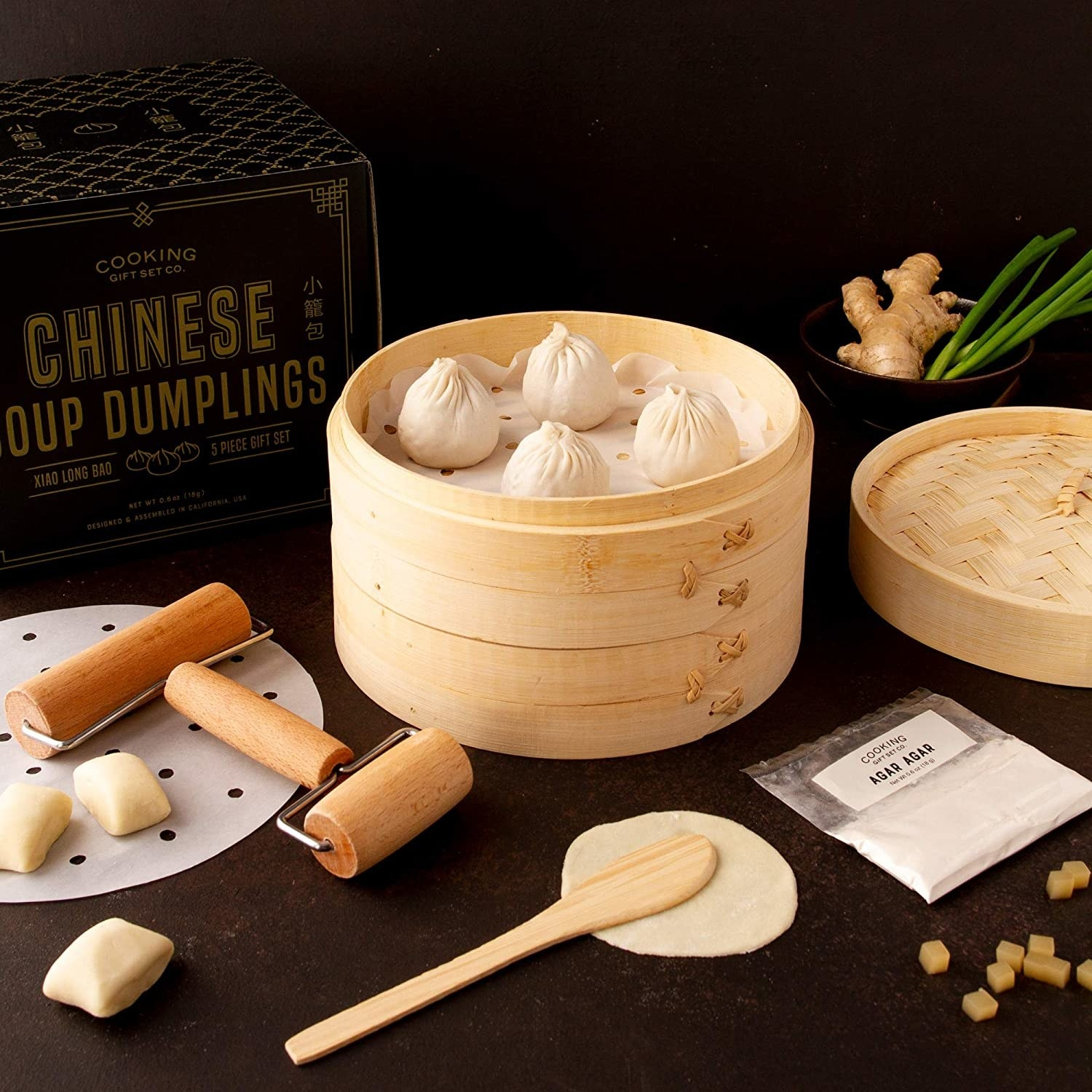 Soup dumplings in wooden basket with tools and dough out around them