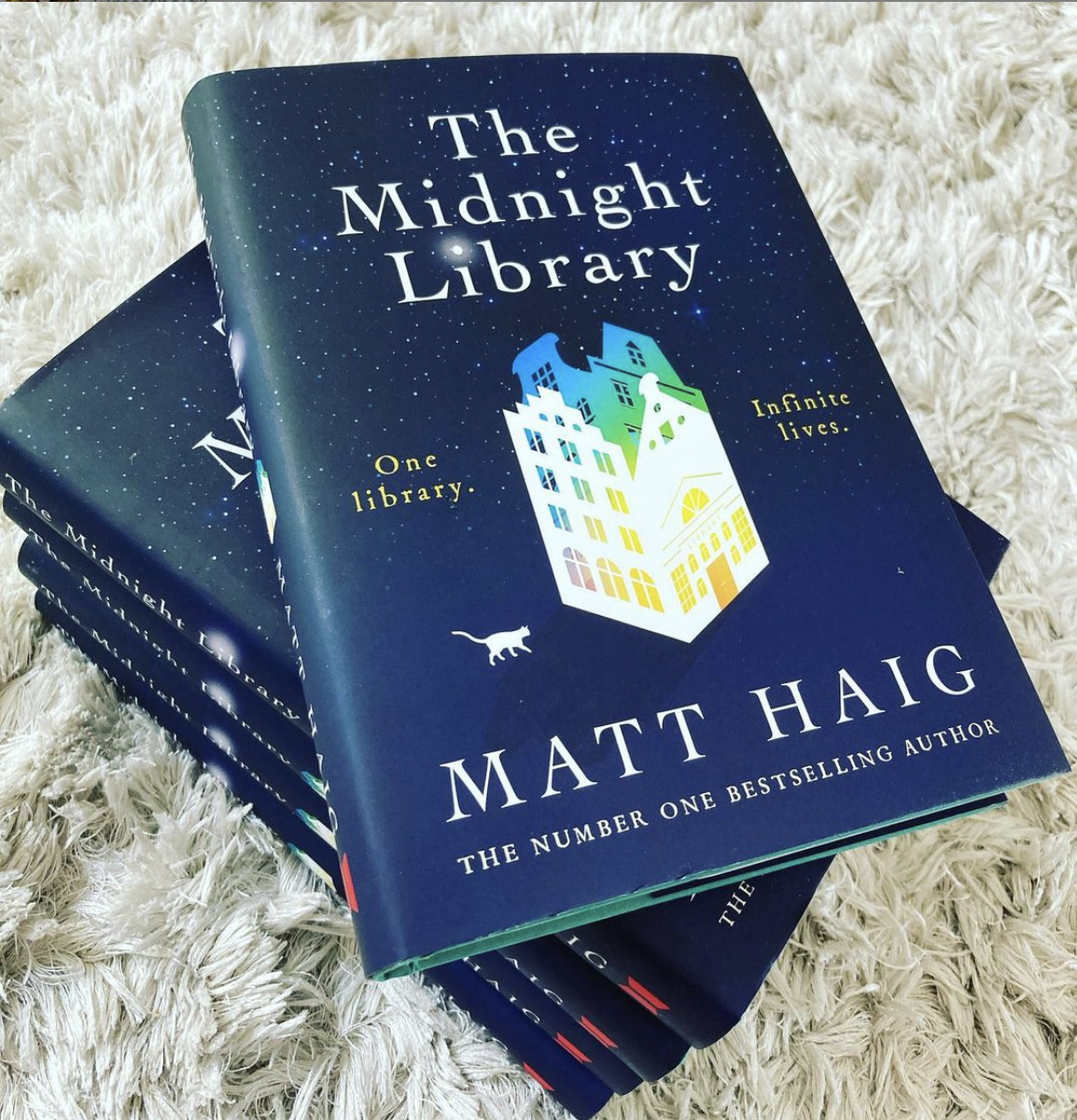 a stack of five copies of The Midnight Library with the text one library, infinite lives