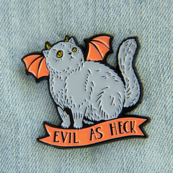 """pin of a gray cat with orange bat wings that says """"evil as heck"""""""