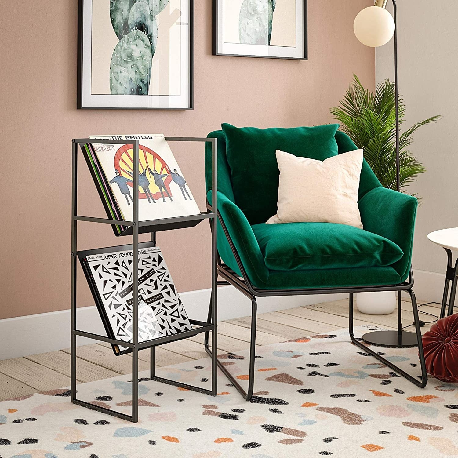 green chair with a shelf beside it with two tiers that hold vinyl records