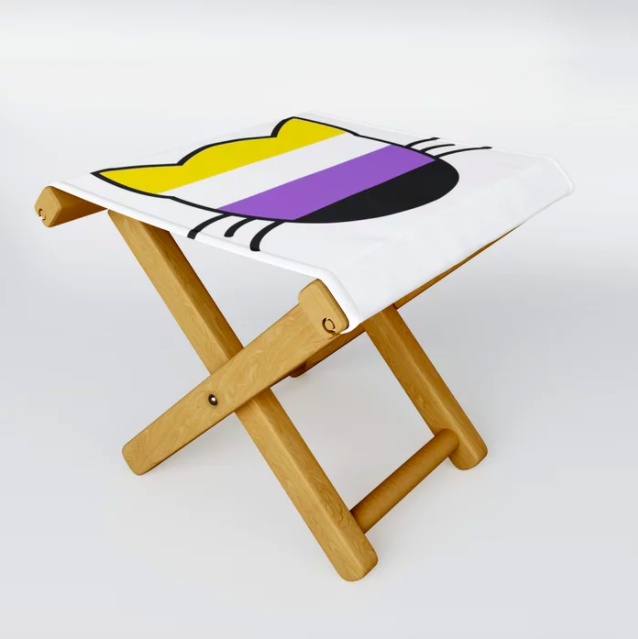 a folding stool with a nonbinary pride cat face printed on the top