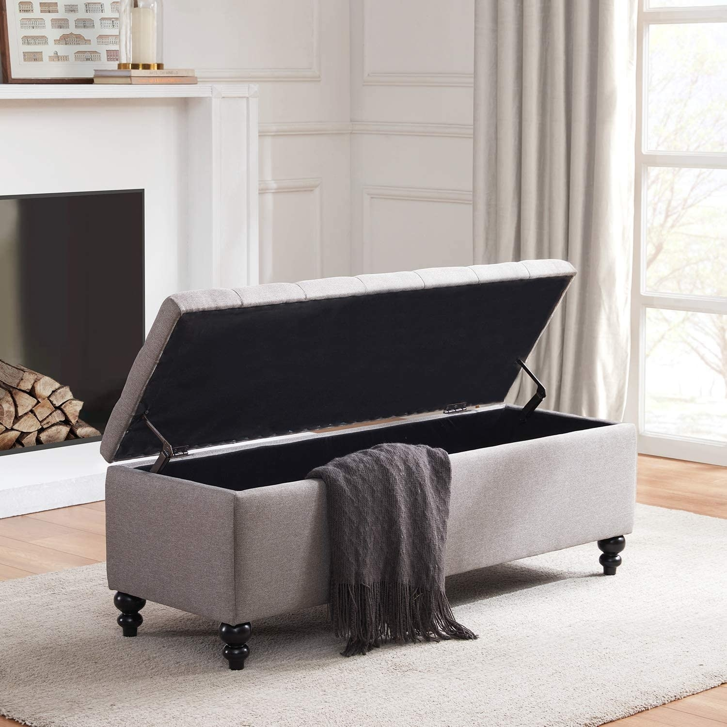 long rectangle light gray open ottoman open with a blanket in it