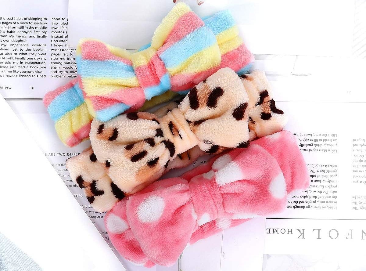 Three fluffy headbands with bows at the front lying on a sheet of paper