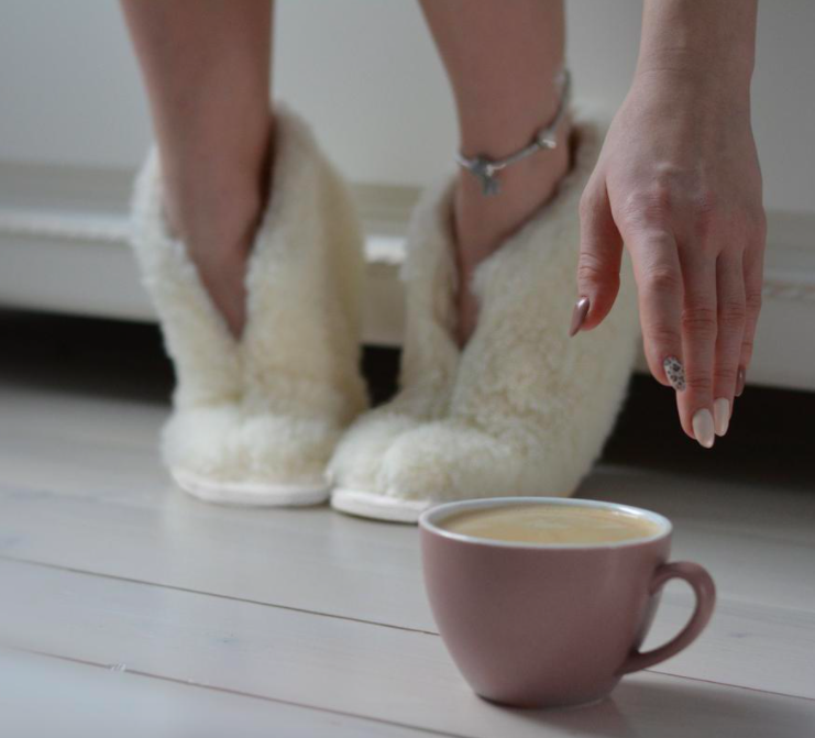 A person wears a pair of the wool slippers while reaching for a cup of coffee on the floor