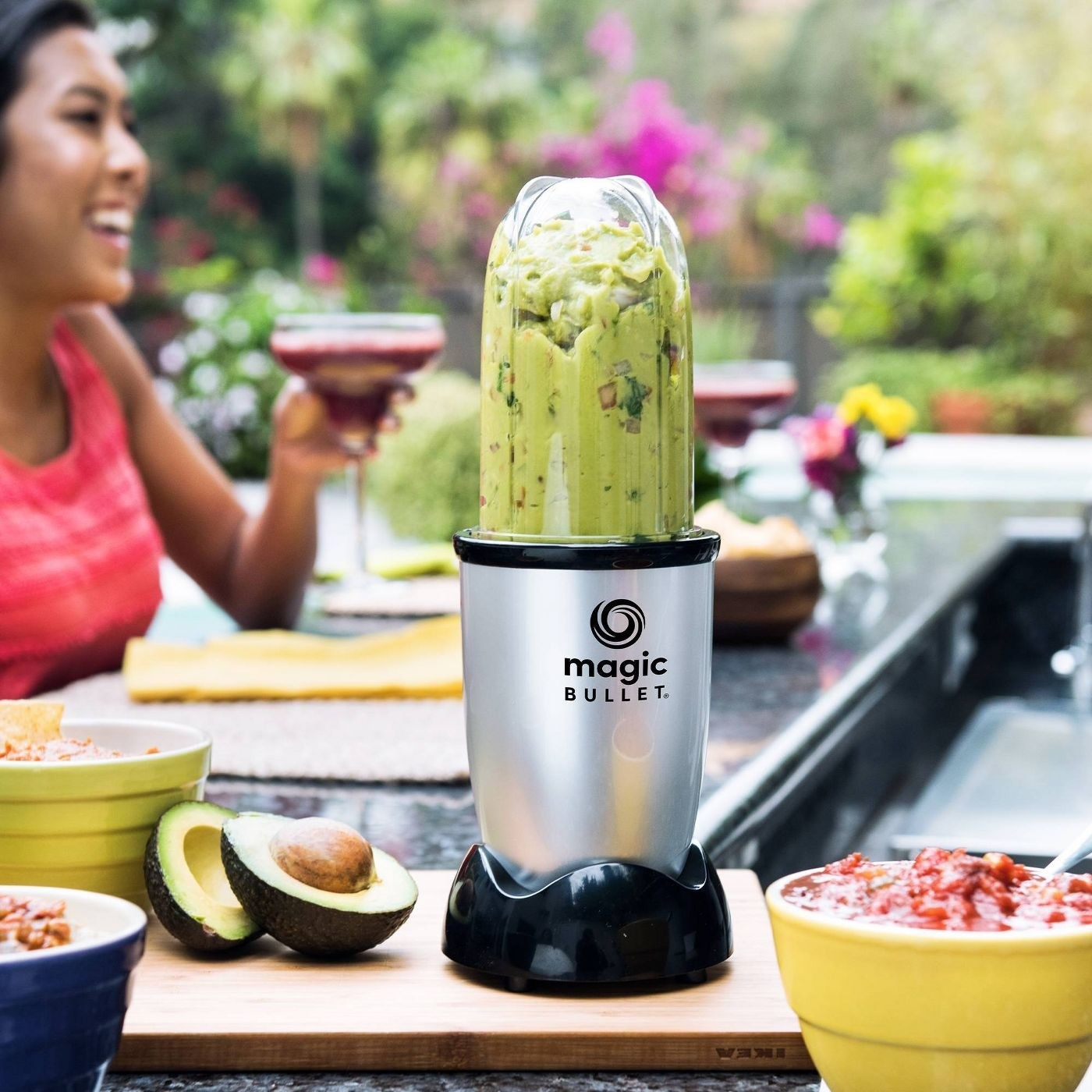 magic bullet with guacamole in it in the foreground and a woman drinking a margarita in the background
