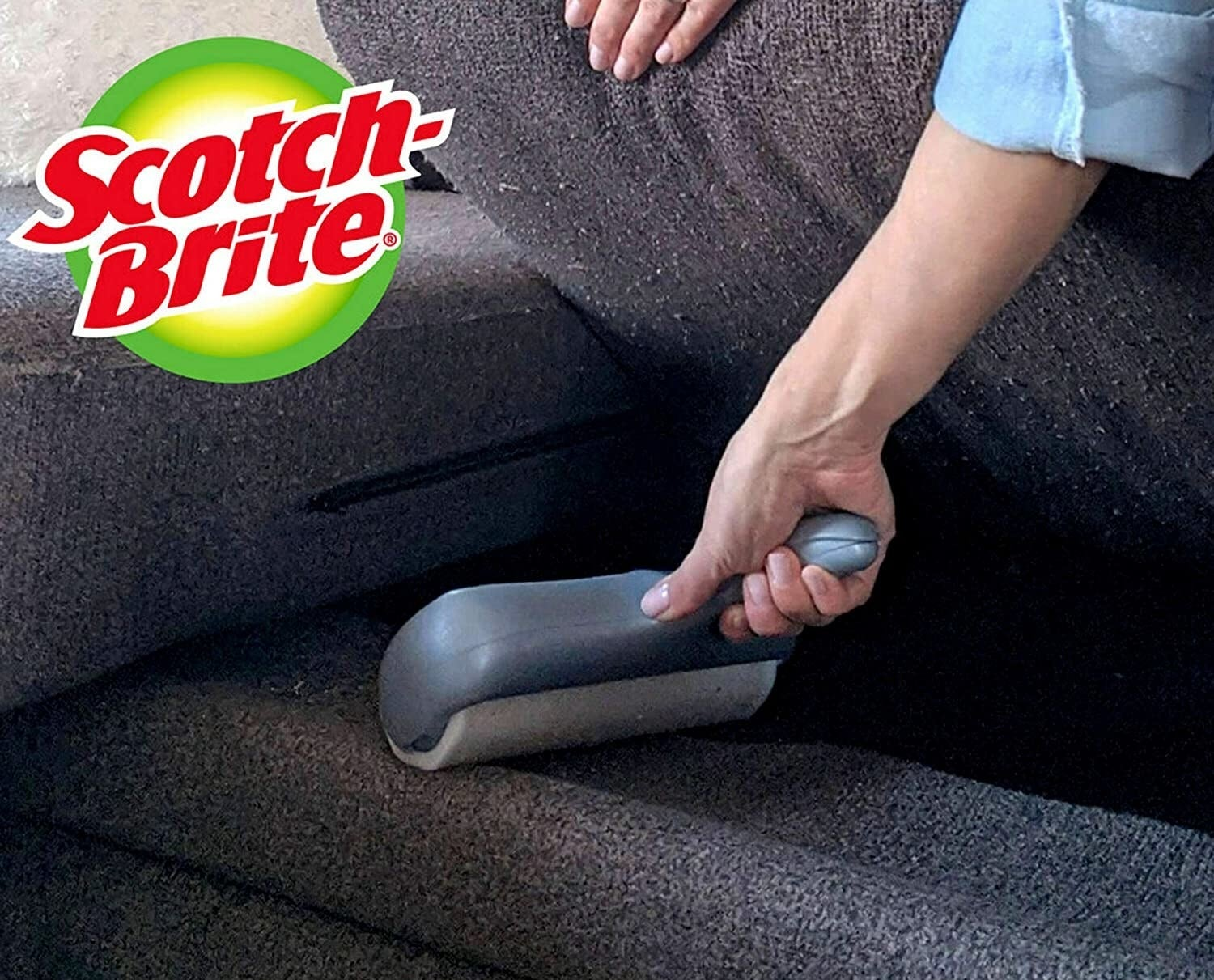 person rolling under a couch cushion with the large lint roller