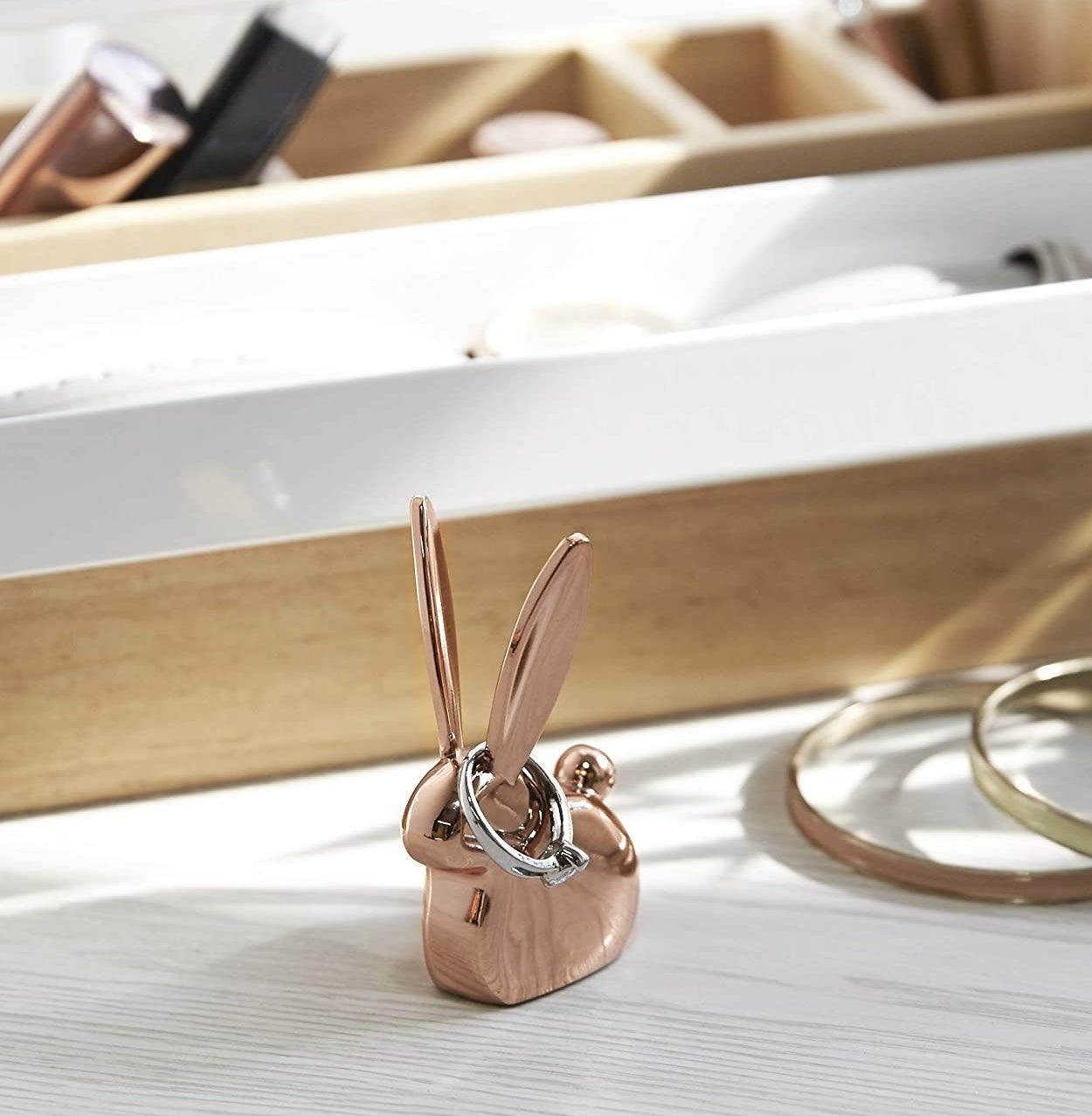 A rabbit-shaped ring holder on a dresser