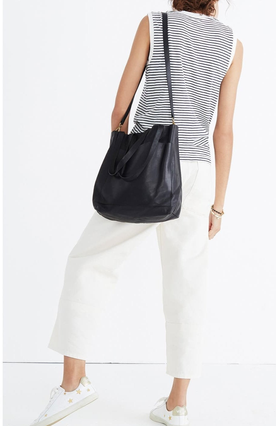 The black leather tote bag with shoulder straps over a model's shoulder and a large pocket on the front with shorter straps