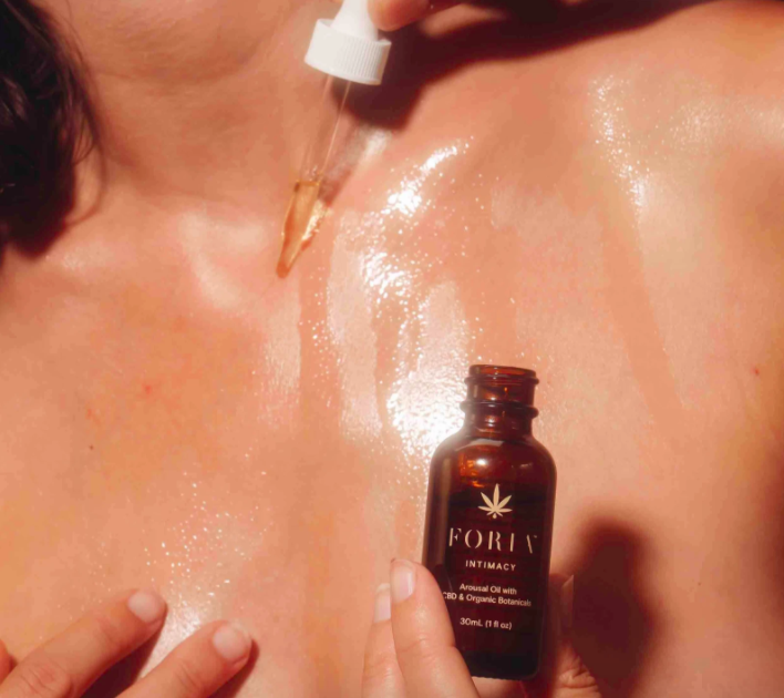 A model drips Foria intimacy and arousal oil on their chest