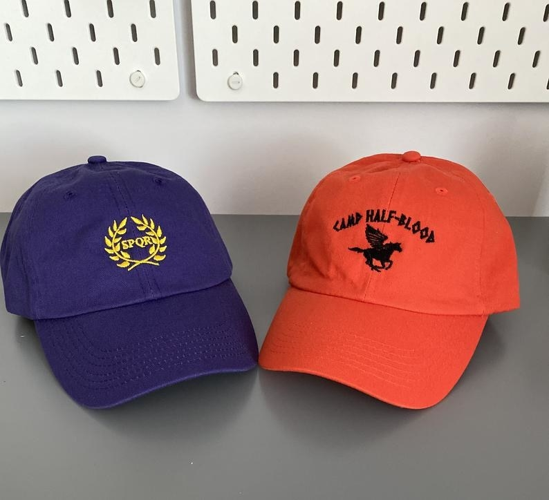 Two baseball caps, one purple with a gold SPQR symbol and one orange with a black Camp Half-Blood pegasus logo