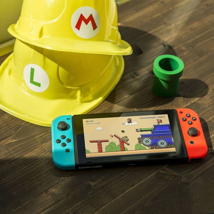A blue and red Nintendo switch handheld on top of a wooden table with two yellow hats in the background, one with an M for Mario and another with an L for Luigi
