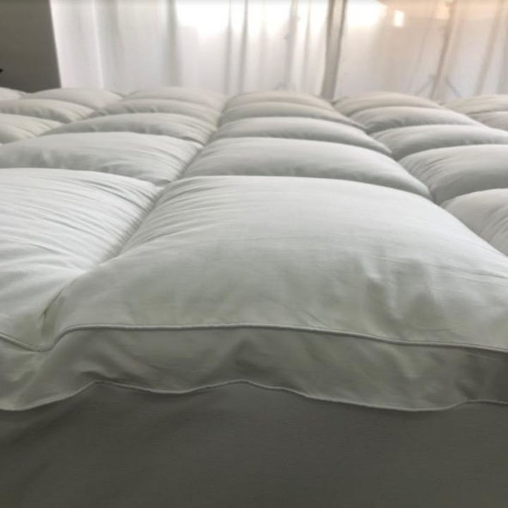 A reviewer's photo which shows the loft of the mattress topper