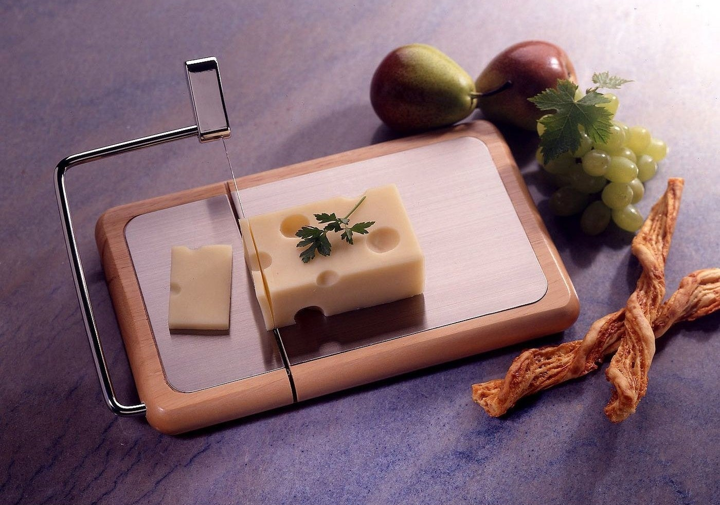 a cheese slicer cutting through a block of cheese on a metal and wood tray