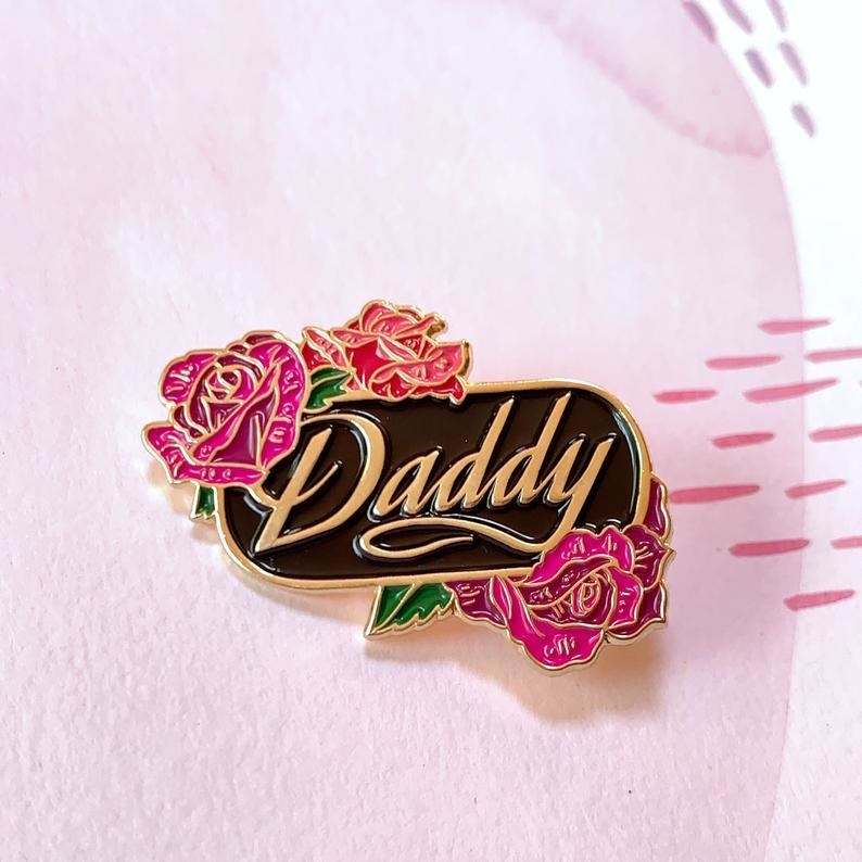 a Daddy pin with gold letter, a black background and roses
