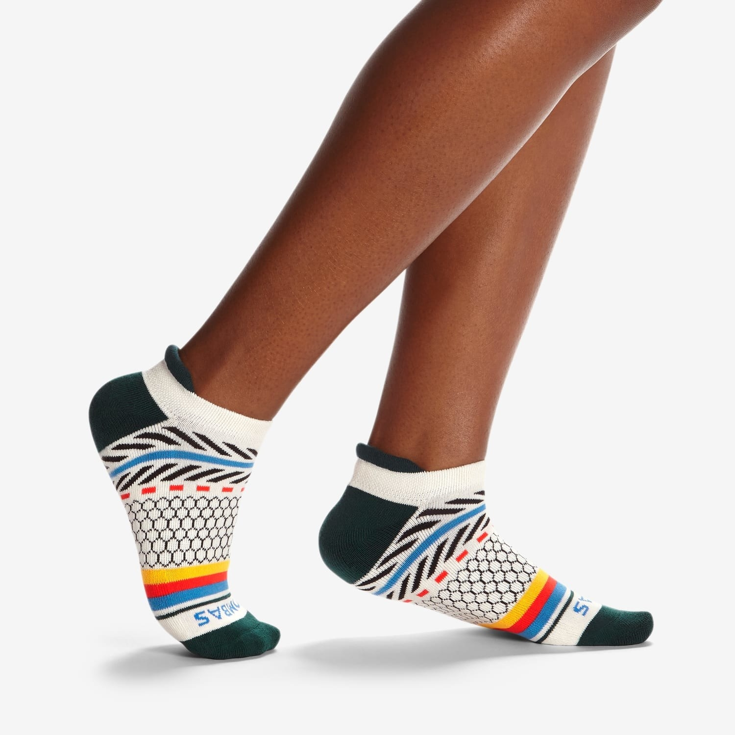A model's feet in white socks with green toes and heel, a navy, blue, and red pattern around the back of the foot, and a yellow, red, and blue pattern around the mid-foot
