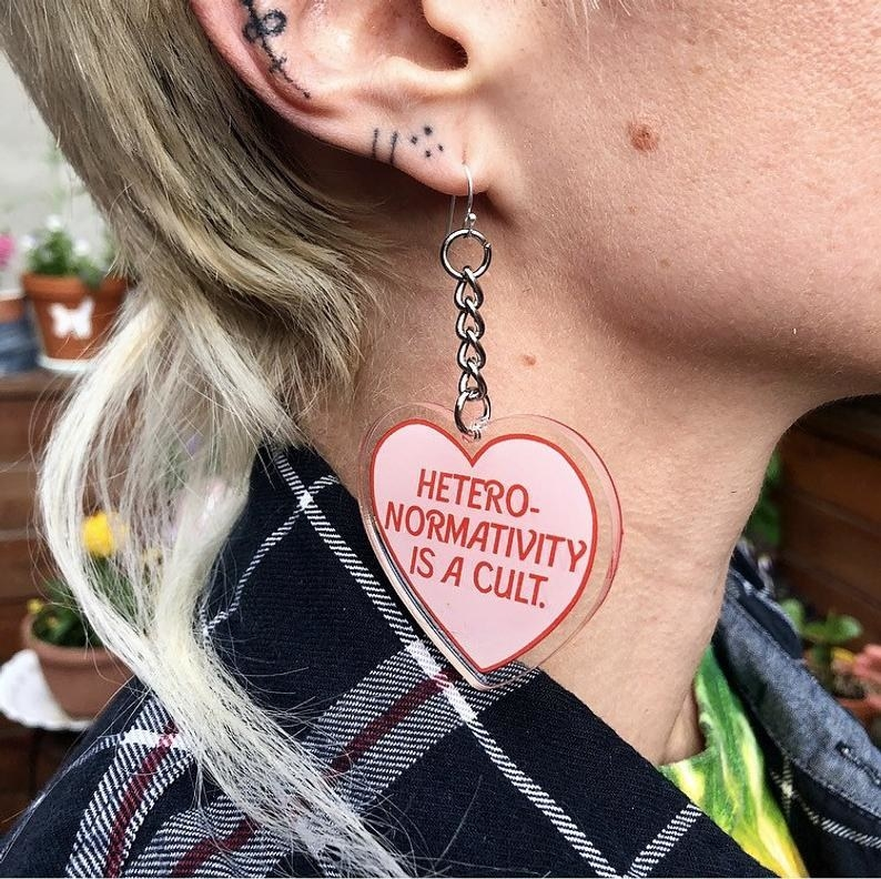 "a pair of heart-shaped earrings that read ""hetero-normativity is a cult"""