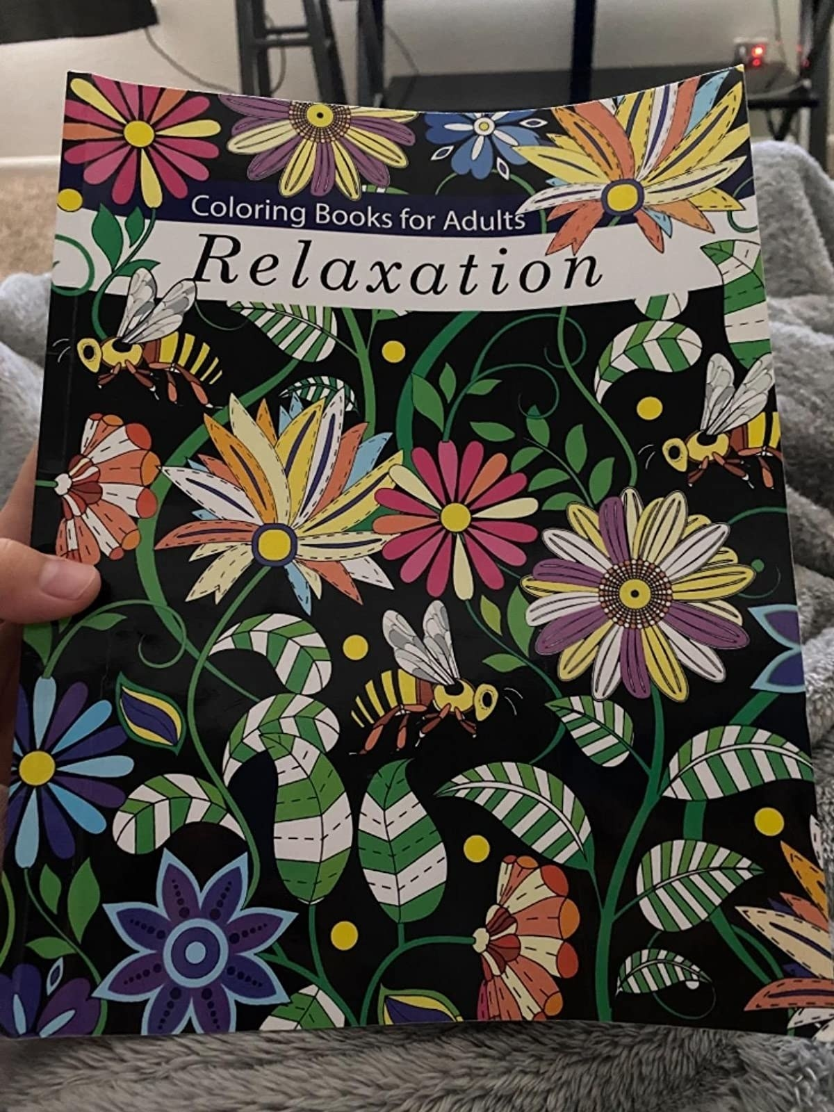 A reviewer holds up the cover of Coloring Books for Adults: Relaxation, depicting flowers and insects, that they purchased off of Amazon