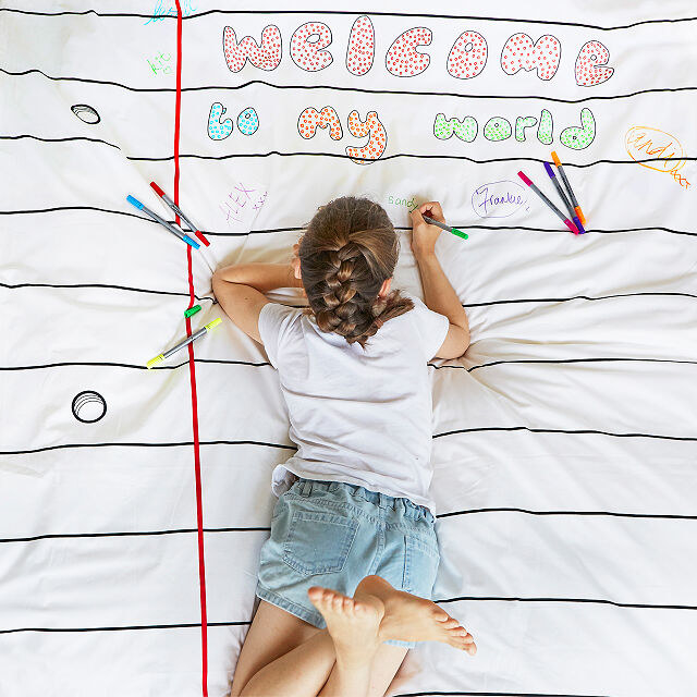 A child drawing with the markers on the lined paper duvet cover