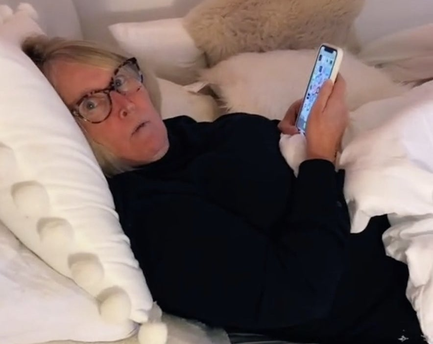 A mom looks shocked while laying in bed