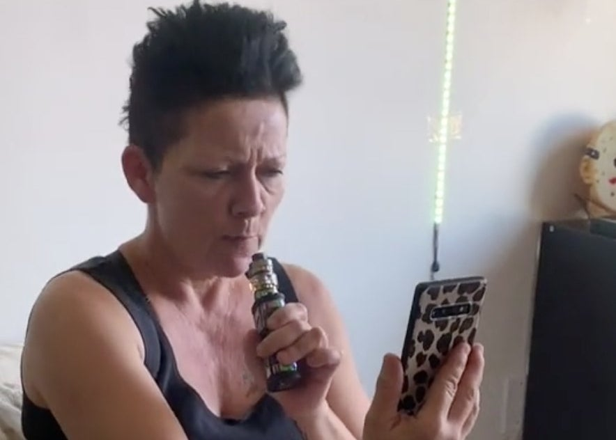 A mom looks at her phone while using her vape