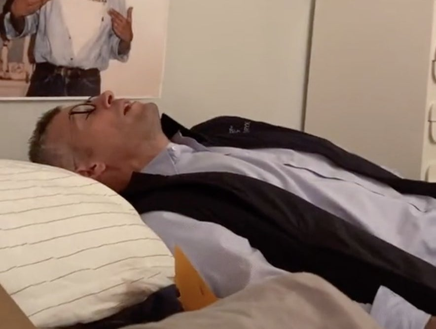 A dad looks exacerbated while lying in bed