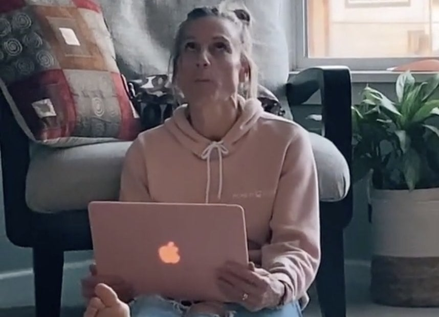 A mom rolls her eyes while looking at a laptop