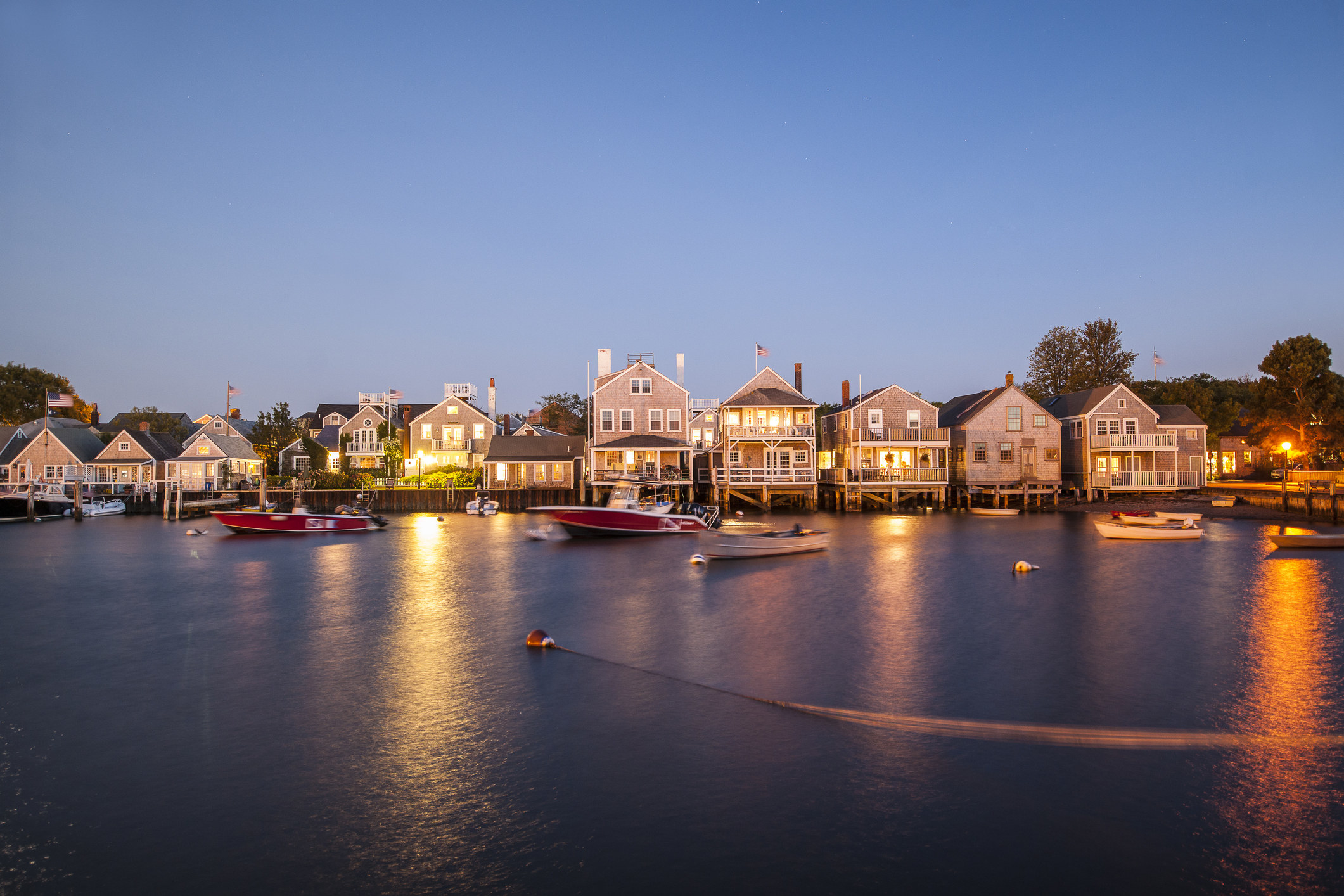 a row of cute houses along the waterfront at dusk
