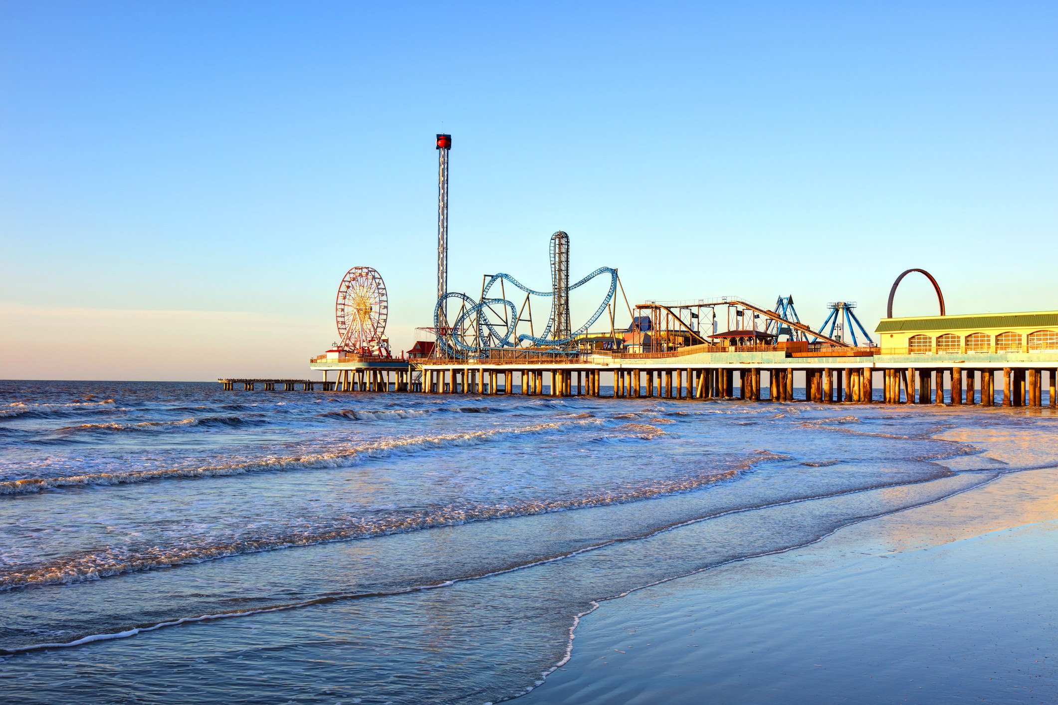 Island pier with amusement park rides and a beach