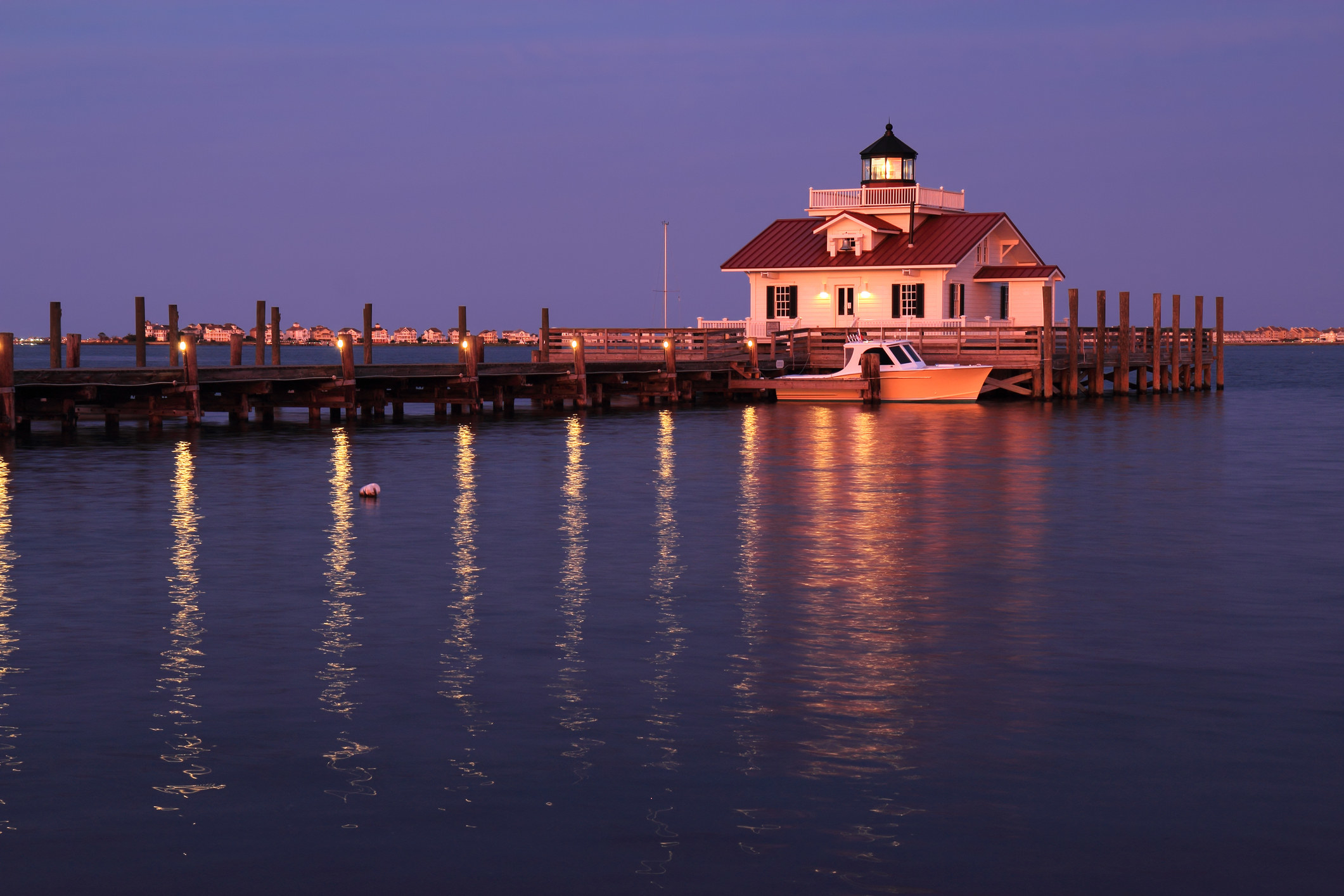 A lit up pier with a building at the end and soft dusk light