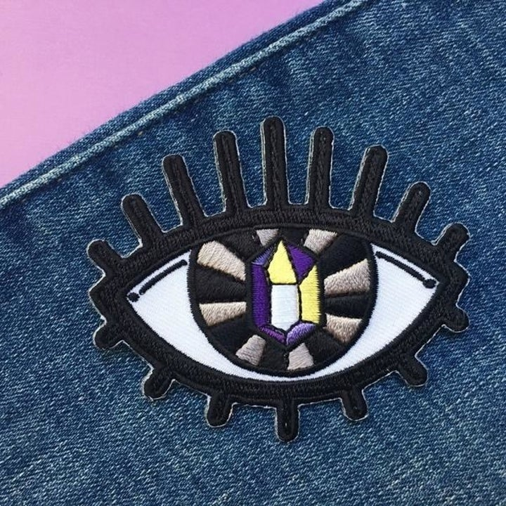 an iron-on patch in the shape of an eye with a nonbinary pride colored gem as the pupil